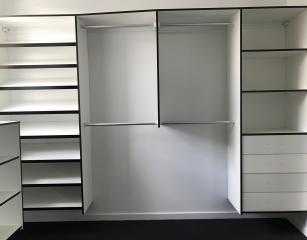 Sloping shoe shelves with half hang and bank of shelves with drawers. All white with Black edge